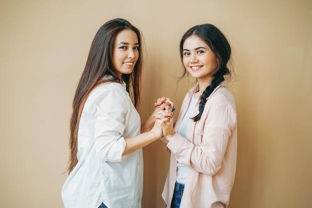 Jeunes étudiants filles amis souriant en casual isolé sur fond beige