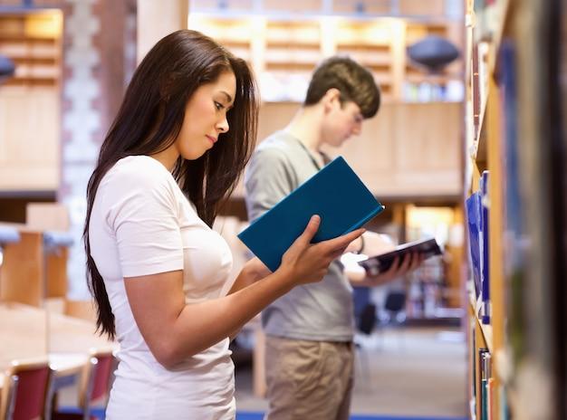 Jeunes étudiants lisant un livre en se levant