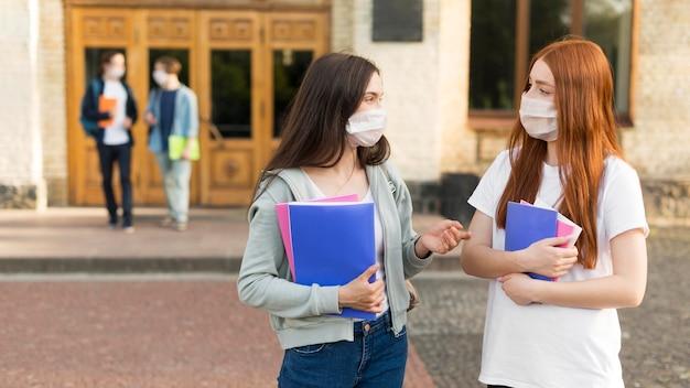 Jeunes étudiants avec des masques faciaux discutant