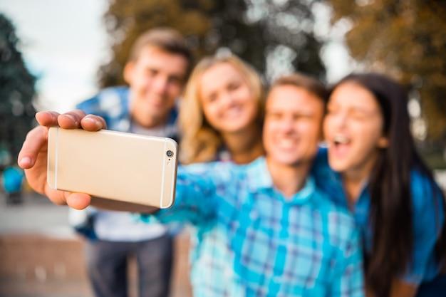 Jeunes étudiants prenant selfie dans le parc ensemble
