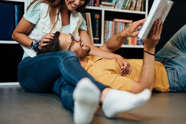 Jeunes étudiants séduisants homme et femme assis dans la bibliothèque universitaire et apprenant.