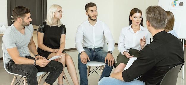Jeunes étudiants universitaires ayant une discussion de groupe assis ensemble sur un cercle