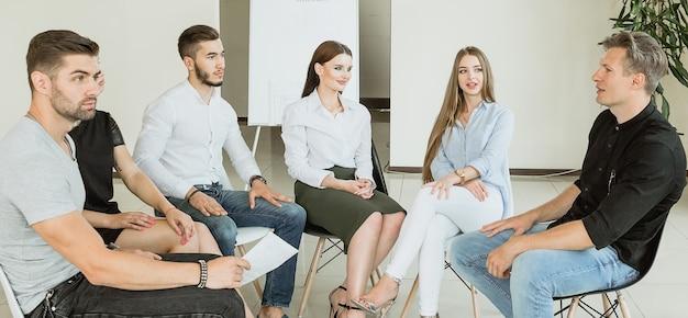 Jeunes étudiants universitaires souriant et parlant avec un tableau visible derrière