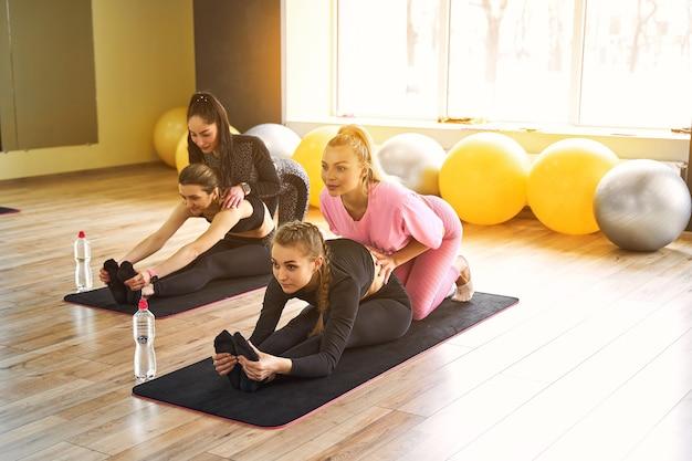 Jeunes femmes actives au corps mince faisant des exercices d'étirement pour garder la flexibilité du corps en forme sur un tapis de yoga