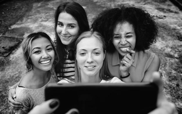 Jeunes femmes adultes amis prenant un groupe selfie