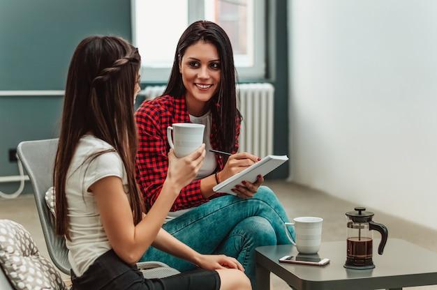 Jeunes femmes d'affaires assis au bureau, se regardant et souriant.