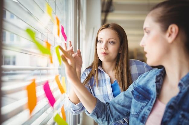 Jeunes femmes d'affaires discutant sur des notes adhésives sur la fenêtre