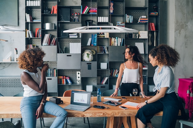 Jeunes femmes d'affaires multiraciales ayant une réunion informelle dans un bureau de coworking moderne