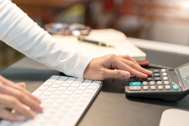 Jeunes femmes d'affaires en tapant sur la calculatrice au bureau