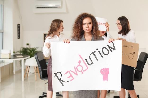 Jeunes femmes avec affiche au bureau. concept de féminisme