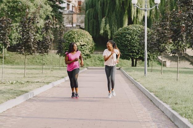 Jeunes femmes africaines en bonne santé à l'extérieur dans le parc du matin. formation d'amis.