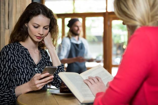 Les jeunes femmes à l'aide de téléphone et livre de lecture à table dans un café