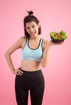 Les jeunes femmes aiment manger des légumes sur une rose.