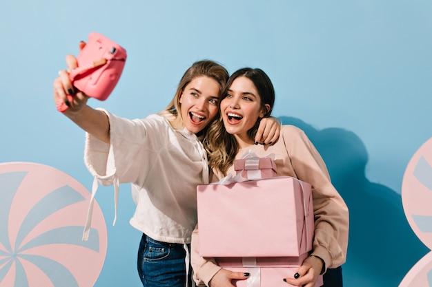 Jeunes femmes avec appareil photo rose prenant selfie