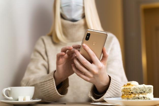 Les jeunes femmes asiatiques à l'aide d'un téléphone intelligent avec des masques chirurgicaux au bureau.