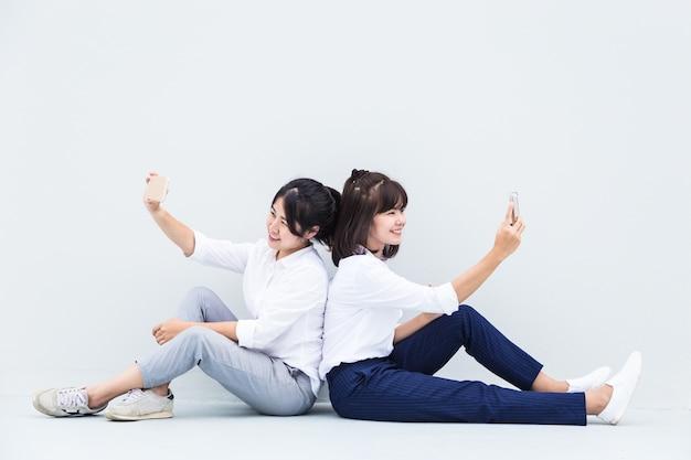 Les jeunes femmes asiatiques aiment prendre leurs selfies à partager sur les réseaux sociaux