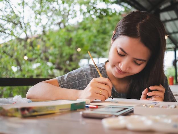 Jeunes femmes asiatiques attrayantes peint sur une table en bois avec un visage heureux