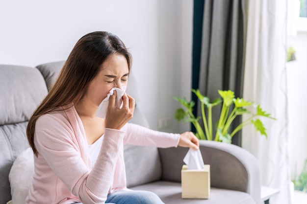 Les jeunes femmes asiatiques souffrant d'allergies se sentent mal à l'aide de tissus et éternuements à la maison