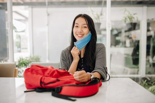 Les jeunes femmes asiatiques sourient avec un masque de protection. elle est assise au bureau ou en classe. concept de prévention du virus covid-19.