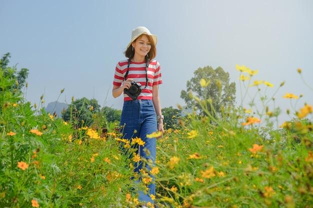 Jeunes femmes asiatiques voyageant tenant la caméra voyageant jardin