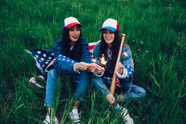 Jeunes femmes assis sur l'herbe verte avec le drapeau américain