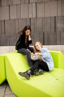 Jeunes femmes assises dans la ville et utilisent un téléphone portable. concept urbain.