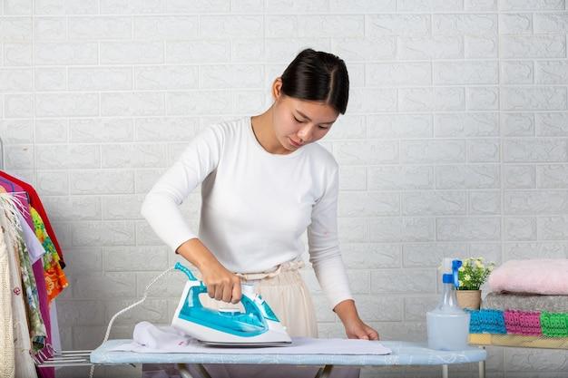 Jeunes femmes au foyer qui utilisent un fer à repasser repassant ses vêtements sur une brique blanche.