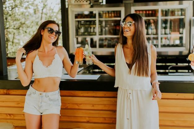 Jeunes femmes buvant un cocktail et s'amusant au bord de la piscine