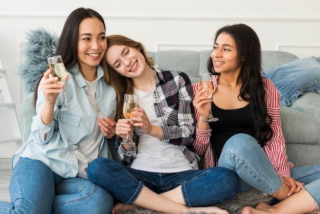 Jeunes femmes buvant du champagne à la maison