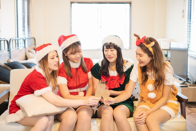 Jeunes femmes célébrant une fête de noël avec le costume de père noël