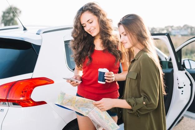 Jeunes femmes cherchant chemin avec carte routière