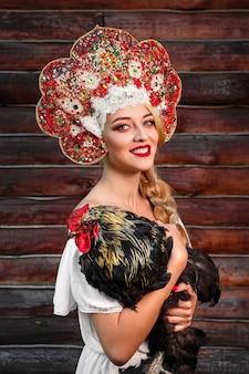 Les jeunes femmes à la coiffure rouge et le style folklorique russe tiennent le coq sur le bois foncé. conte de fées russe