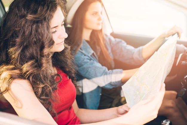 Jeunes femmes conduisant une voiture avec carte