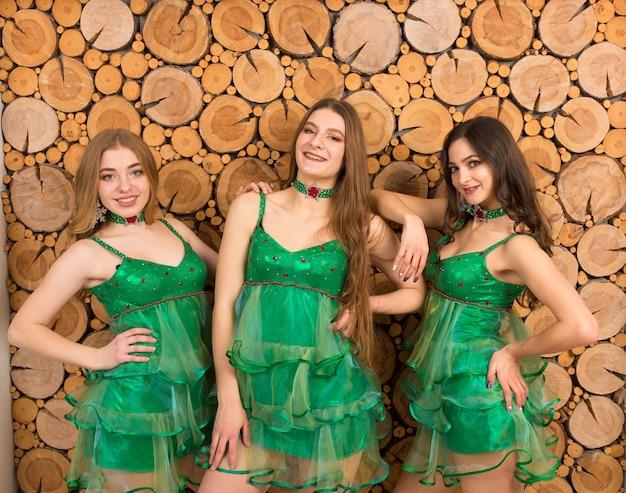 Jeunes femmes en costume d'arbre de noël sexy sur fond en bois, studio