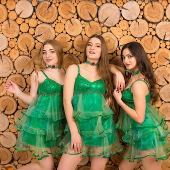 Jeunes femmes en costume d'arbre de noël sexy sur fond en bois en studio