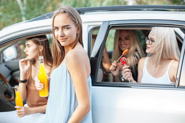 Les jeunes femmes dans la voiture en souriant et en buvant du jus