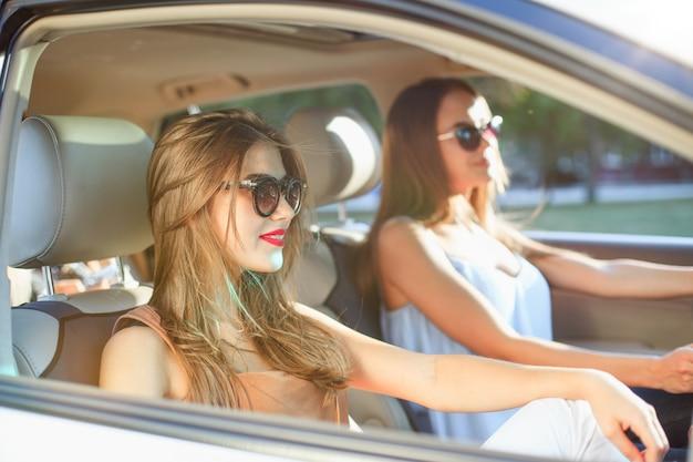 Jeunes femmes, dans voiture, sourire