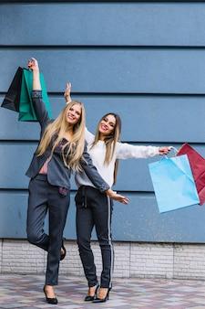 Jeunes femmes, debout, devant, mur, lever mains, tenue, sacs provisions