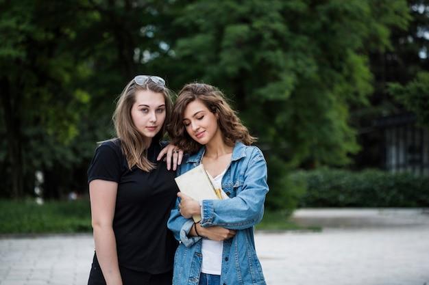 Jeunes femmes décontractées, debout sur le trottoir du parc