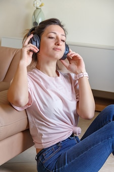 Les jeunes femmes écoutant de la musique avec des écouteurs assis près du canapé beige à la maison