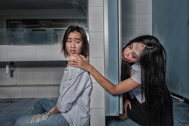 Jeunes femmes effrayantes fantôme universitaire dans les toilettes
