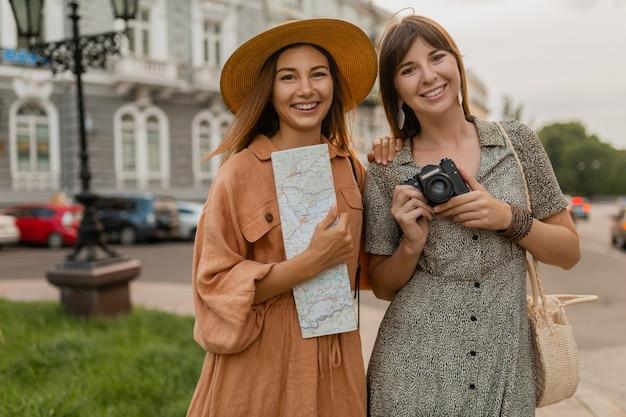 Jeunes femmes élégantes voyageant ensemble en europe vêtues de robes et d'accessoires à la mode du printemps