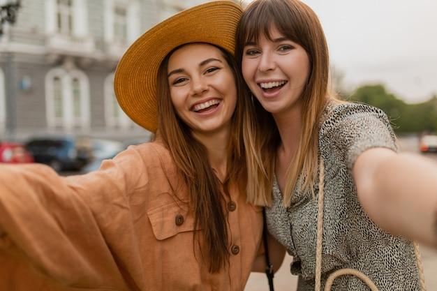Jeunes femmes élégantes voyageant ensemble vêtues de robes et d'accessoires à la mode du printemps s'amusant à prendre une photo de selfie à la caméra