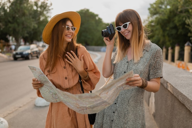 Jeunes femmes élégantes voyageant ensemble vêtues de robes et d'accessoires à la mode du printemps s'amusant à prendre des photos sur une caméra tenant une carte