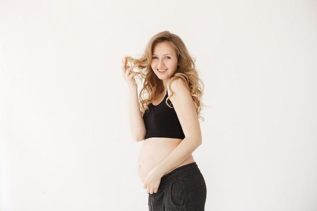 Jeunes femmes enceintes gaies avec des cheveux clairs et ondulés en tenue de sport confortable souriant, tenant les cheveux avec la main, touchant le ventre