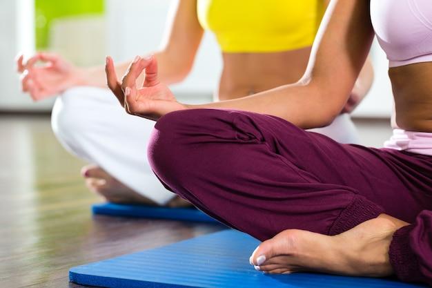 Jeunes femmes faisant du yoga et de la méditation dans une salle de sport pour une meilleure forme physique, caucasiens et latins