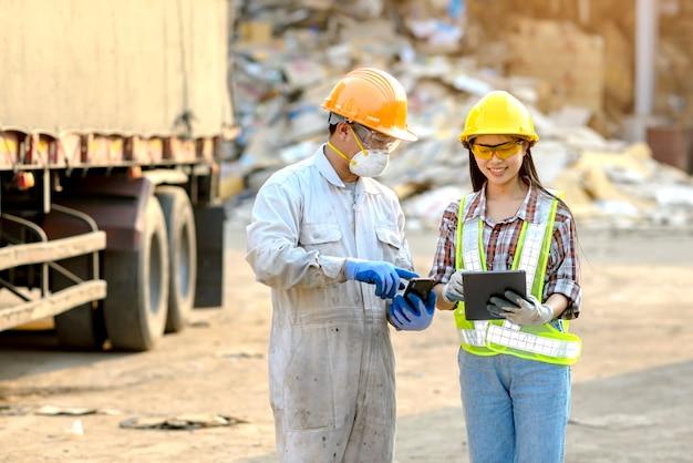 Jeunes femmes, gardiennes de biens et jeunes travailleurs masculins utilisant actuellement la tablette de produit avant d'exporter pour la vente