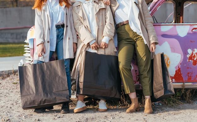Jeunes femmes heureuses avec des sacs posant près d'une vieille voiture décorée