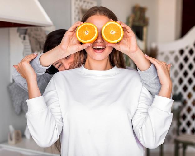 Jeunes femmes jouant avec des oranges