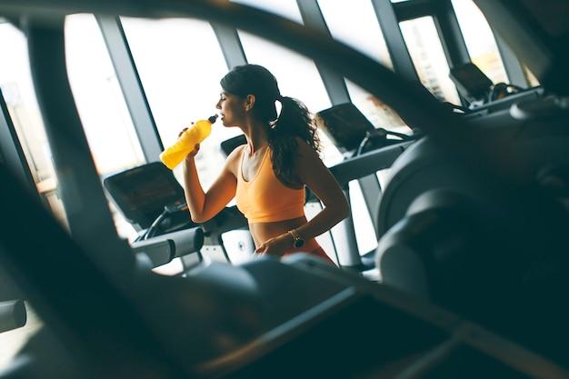 Jeunes femmes en maillot de sport jaune boivent de l'eau à la salle de sport